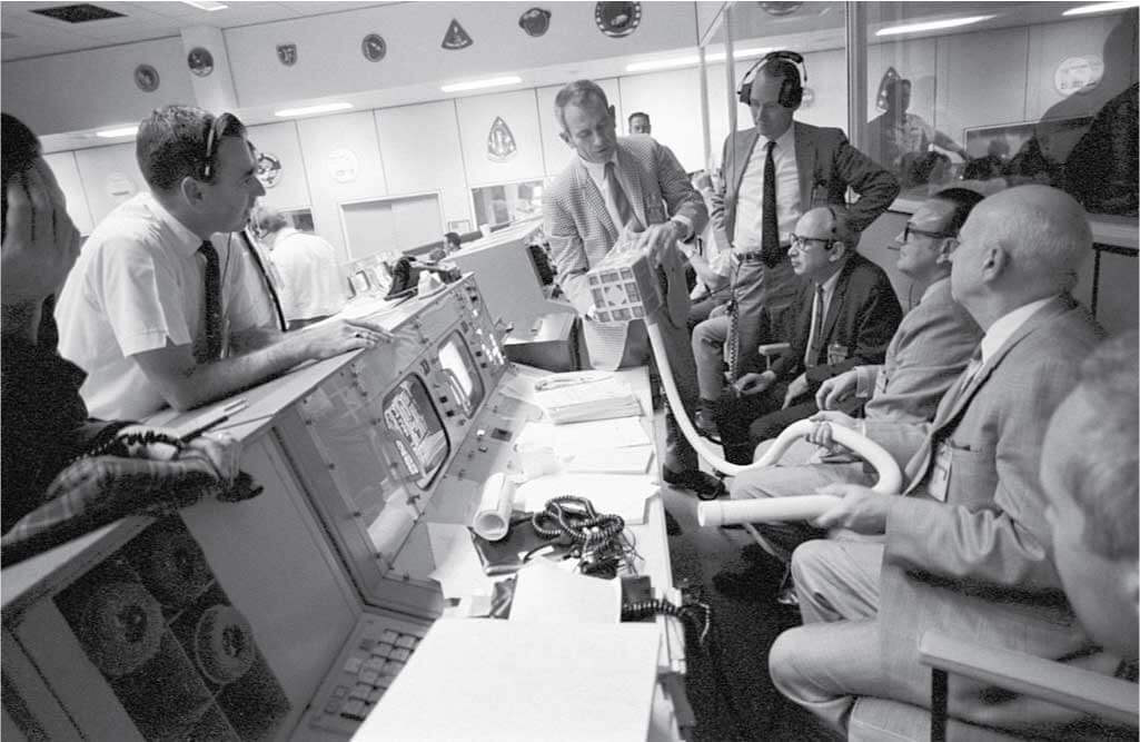 Deke Slayton shows the adapter devised to make use of square Command Module lithium hydroxide canisters to remove excess carbon dioxide from the Apollo 13 LM cabin.