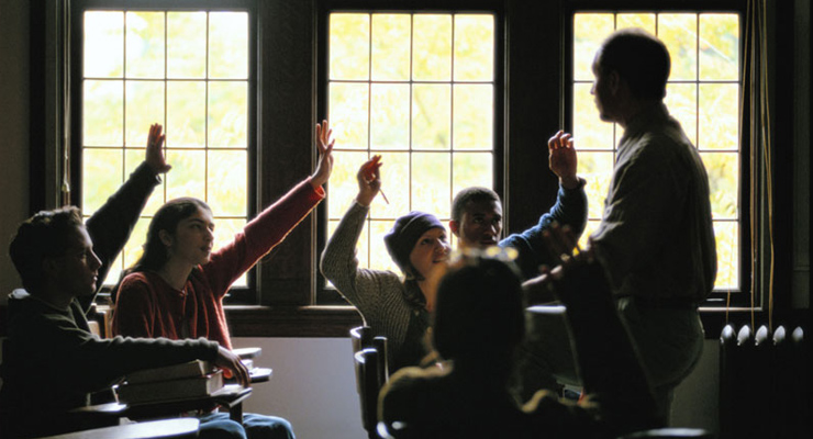 Student in classroom raising hands with teacher standing nearby