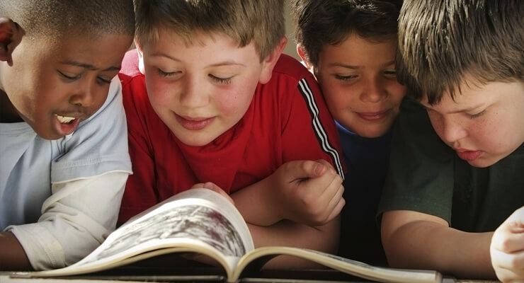 Photo of young school children reading a book together