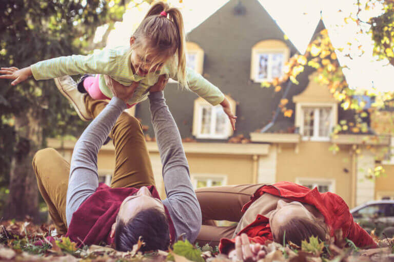 Family playing on lawn in front of their home